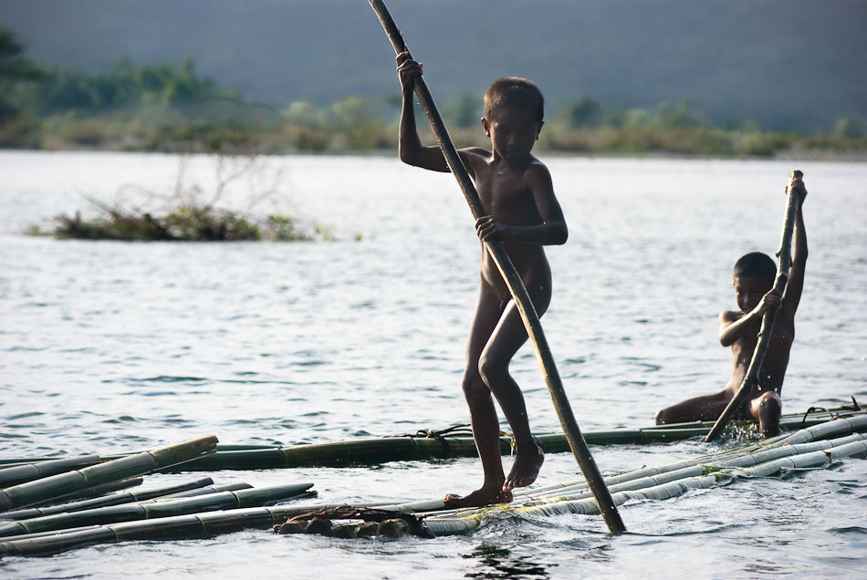 Two boys pushing a bamboo raft on the Cagayan River.