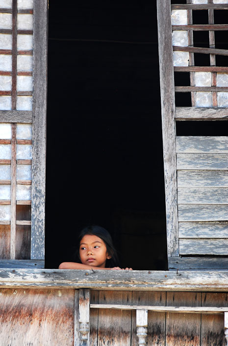A Filipina child looking out of an old capiz shell window in Surigao del Norte.